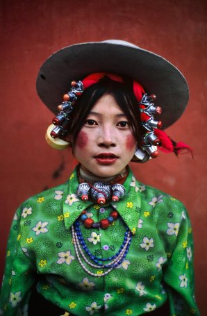 Woman at a horse festival, Tagong, Tibet, 1999McCurry pictured this woman at the famous Tagong horse festival. It is a vivid image. The emerald green shirt, adorned with delicate white flowers, contrasts sharply with the rich blues and reds of the necklaces and rouge applied to the woman's cheeks and lips. All set against a blood red backdrop, it makes for an intoxicating picture.Phaidon, Looking East, The Path to Buddha, Iconic Images, final book_iconic, final print_milanMagnum Photos, NYC31808, MCS1999007K001Each portrait speaks a thousand words about its subject and their world. The intricately carved beads of a festival-goer in Kham, Tibet, unwittingly demonstrate as skill in handicraft that has been almost entirely lost in the West. The striking robes and ceremonial clothing of monks and worshippers at temple are vividly colored by the very same natural dyes and spices that first lured Western traders to Asia. McCurry, Steve. (2006). Looking East. New York: Phaidon Press Inc., 61 final print_milan