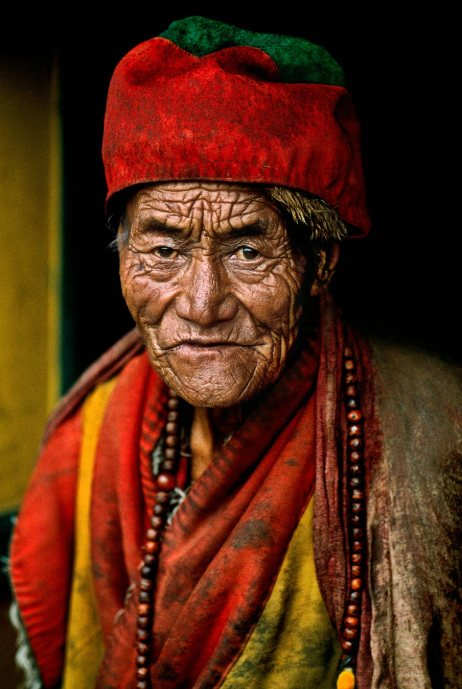 """TIBET-10009, Monk at Jokhang temple, Lhasa, Tibet, 2000'There was something about his face,' McCurry has said of this monk at the Jokhang temple in Lhasa, Tibet. There was some 'ancient feeling, some kind of ancient truth there. I have never seen a face quite like his.' He looks with intensity into McCurry's camera, deeply aware of the transience of the moment.""""The lines of time trace a deep personal history across this old monk's face. It seems as though his has been a life of enquiry, a quest for a truth, on a higher level. He looks into the lens of the camera with a searching gaze. That is what attracted McCurry, as he visited the Jokhang Temple on his photographic pilgrimage through Tibet, sketching with his camera the various pathways to the Buddha. - Phaidon 55Magnum Photos, NYC31836, MCS2000009 K001Phaidon, 55, Looking East, The Path to Buddha, Iconic Images, final print_milan, final book_iconic"""