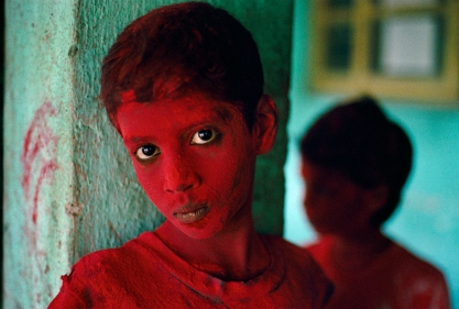 Painted Boy, Bombay, India.1996 Boy participating in the festival of Ganesh Chaturthi is covered with red powder during the exuberant celebration. This festival marks the birthday of the elephant headed deity Lord Ganesh, son of Lord Shiva and Parvati, and one of Hinduism's most popular deities. Praying to Ganesh during the festival is believed to protect one from obstacles in life and bring good luck and prosperity for the family. In the midst of the festival of Ganesh in Bombay, as people young and old processed from their neighbourhoods to the sea, McCurry interrupted a youngster with a request to make his picture. The boy consented, and one reads in his eyes the vulnerability of his acceptance. We see a fragment of festive time, a stilled moment extracted from a noisy, exuberant parade. Yet in that sliver of time, a much larger psychological proposition was created: the boy, framed on the one side by three aggressive slashes of red upon the light face of a pillar; the shadow form of another person at his other side; and the central anchor of his intensely questioning eyes.