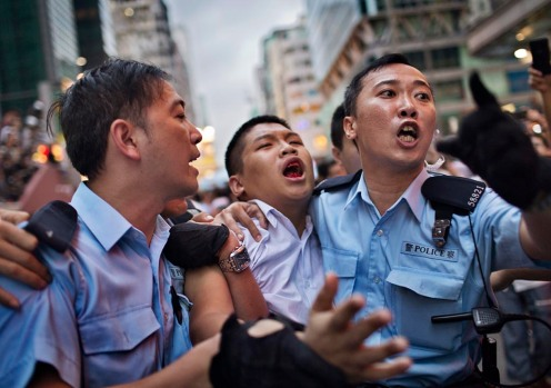 A Pro-democracy protester is escorted from a protest site after men confronted protestors by breaking apart their encampments, surrounding them and tearing down their tents in Mong Kok, Hong Kong on Oct. 3, 2014. Photo by Adam Ferguson for The New York Times NYTCREDIT: Adam Ferguson for The New York Times